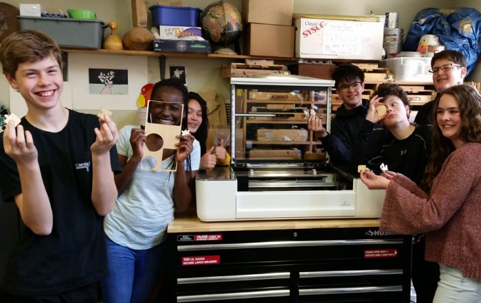 middle school students with laser cutter