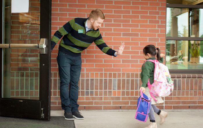 Nick Zosel-Johnson high fives student at front door of lower school