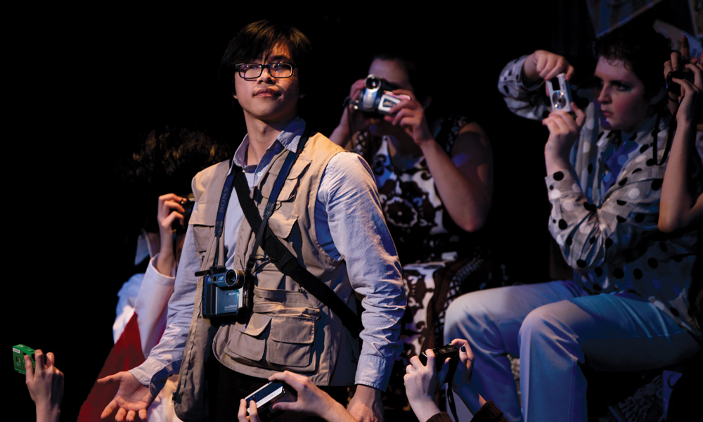 students take photos during scene in upper school play