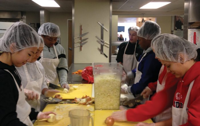 upper school students chop onions in the Tacoma Rescue kitchen