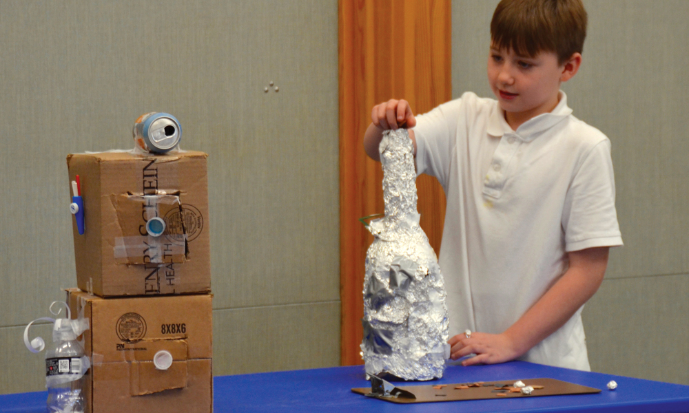student with his mouse trap design made from cardboard boxes and tin foil