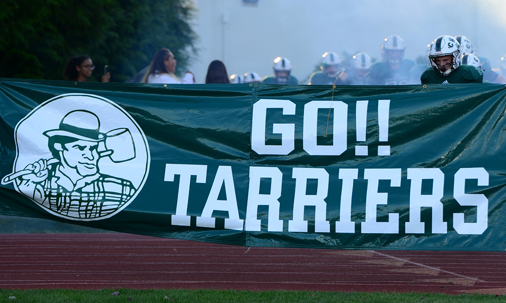 Football players run through banner with the words GO!! Tarriers