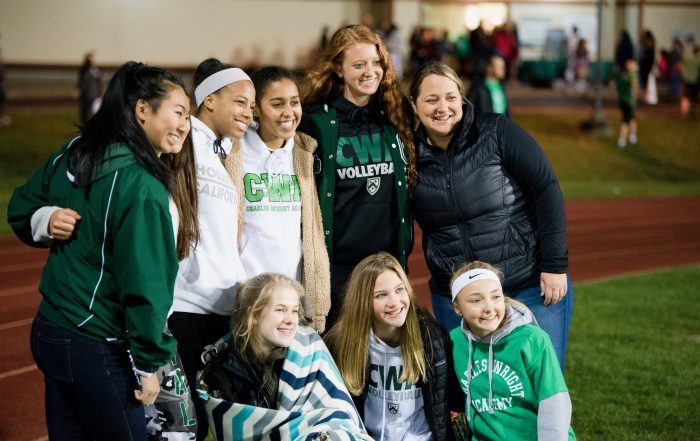 Coach Mindy McGrath poses with female students at Homecoming