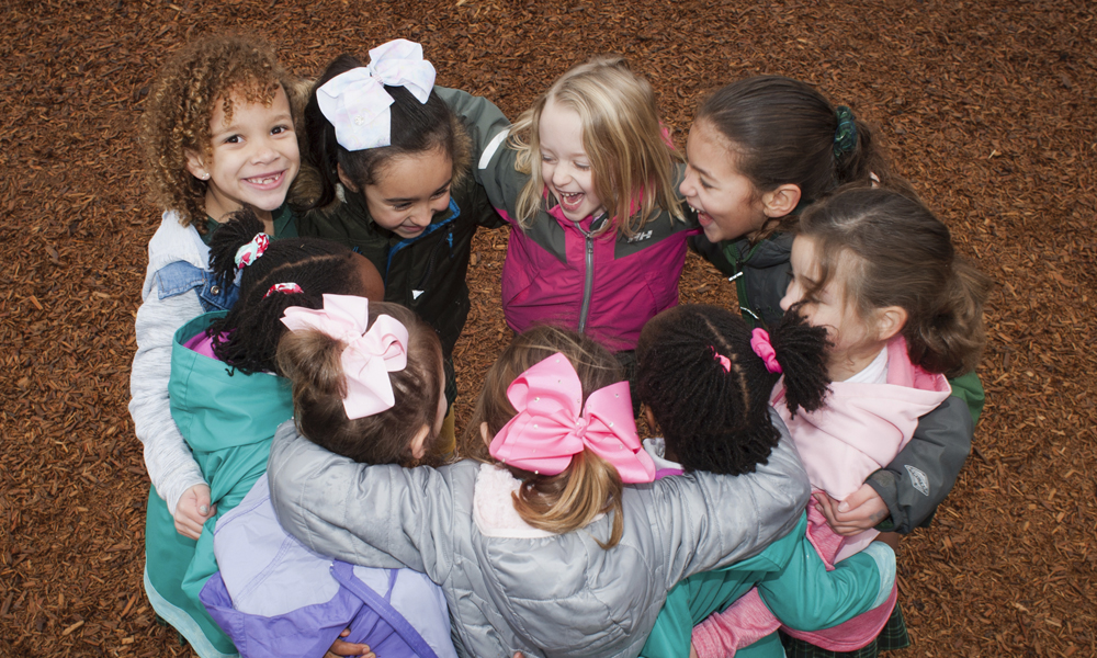 lower school students form a circle on the playground