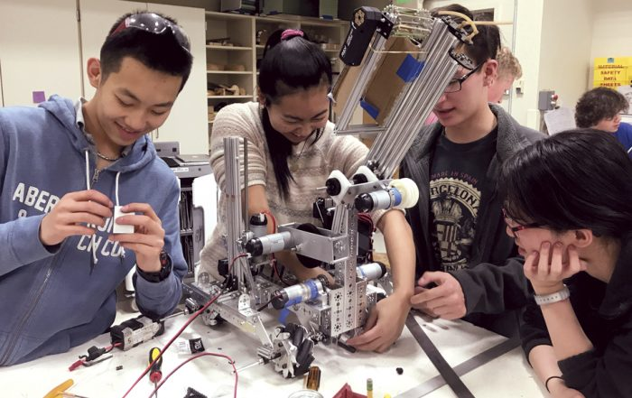 robotics team members work on their robot